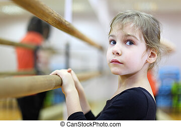 face of little girl in ballet class near frame and large...