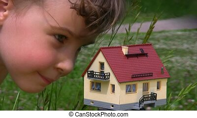 face of little girl looking at toy house