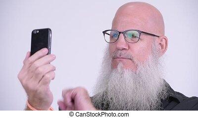 Face of mature bald bearded man using phone