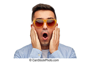 face of scared man in shirt and sunglasses