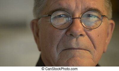Face of senior man with eyeglasses indoors - Portrait of ...