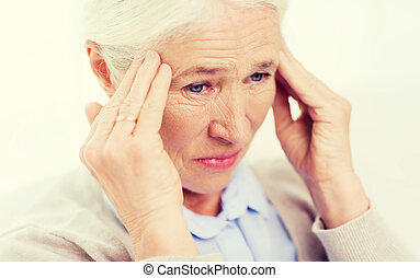 face of senior woman suffering from headache