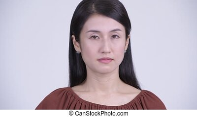 Face of serious Asian woman nodding head no - Studio shot of...