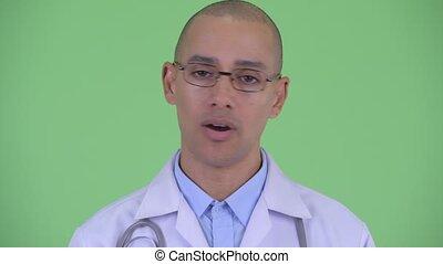Face of serious bald multi ethnic man doctor nodding head no...