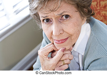 Face of serious elderly woman staring at camera