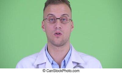 Face of serious man doctor nodding head no - Studio shot of...