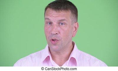 Face of serious mature macho businessman nodding head no -...
