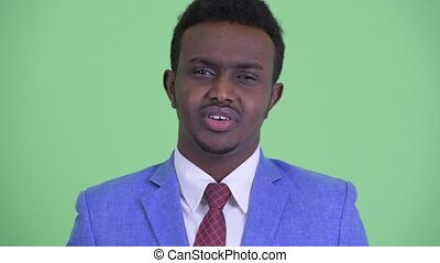 Face of serious young African businessman nodding head no -...