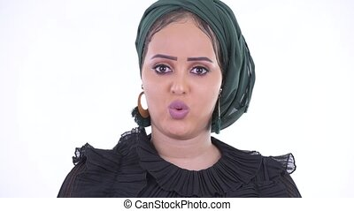 Face of serious young African Muslim woman nodding head no -...