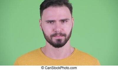 Face of serious young bearded man nodding head no - Studio...
