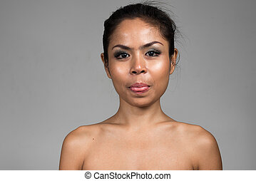 Face of shirtless Asian woman sticking tongue out