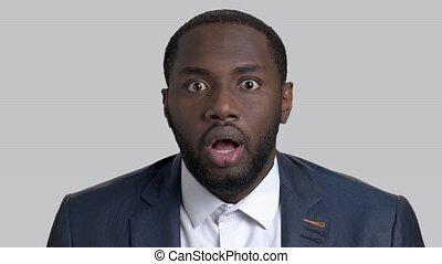 Face of shocked entrepreneur on grey background.
