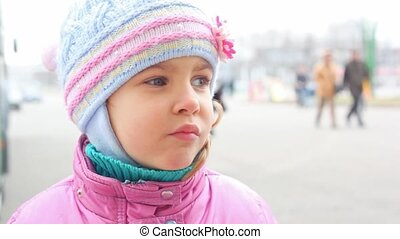 face of small girl standing on street, people walking by