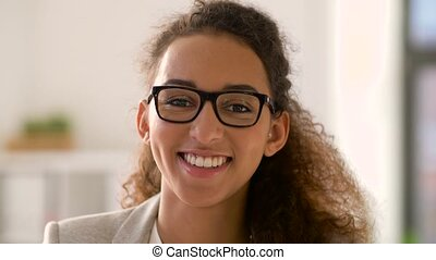 face of smiling african american woman in glasses -...