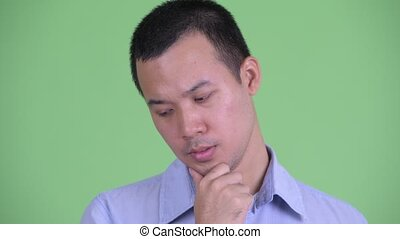 Face of stressed Asian businessman thinking and looking down