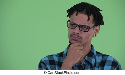 Face of stressed young African hipster man thinking and looking down