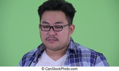 Face of stressed young overweight Asian hipster man thinking...