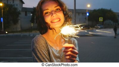 Face of the girl dancing with sparkler in night city