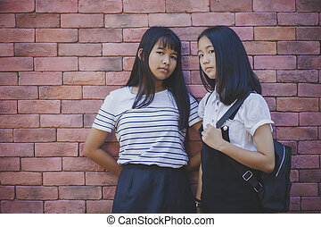 face of two asian teenager standing and looking to camera...