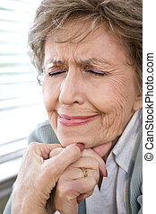 Face of upset elderly woman with eyes closed - Face of upset...