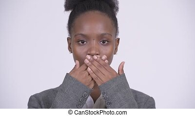 Face of young African businesswoman covering mouth as three...