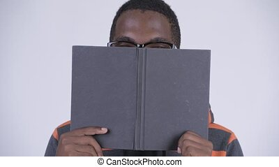 Face of young African nerd man covering face with book