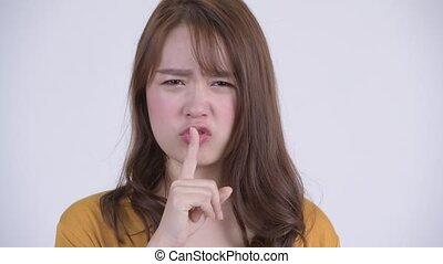 Face of young angry Asian woman with finger on lips