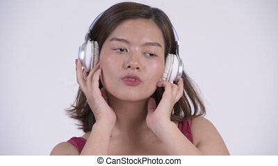Face of young Asian tourist woman listening to music