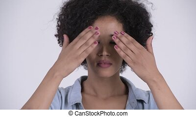 Face of young beautiful African woman covering eyes as three...