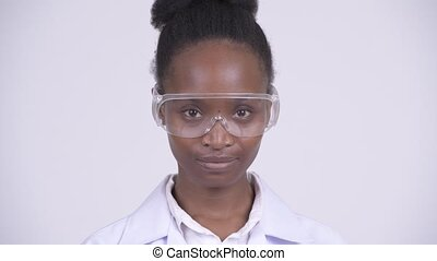 Face of young beautiful African woman doctor wearing protective glasses