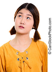 Face of young beautiful Asian woman thinking