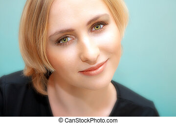 face of young blond woman with green eyes