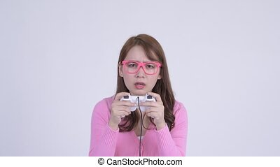 Face of young focused Asian nerd woman playing games -...
