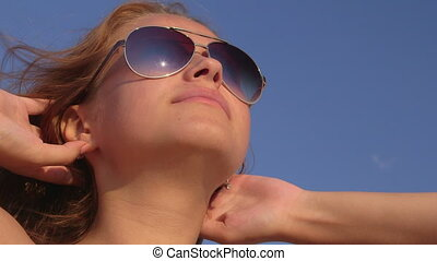 Face of young girl in sunglasses sunbathing on the beach