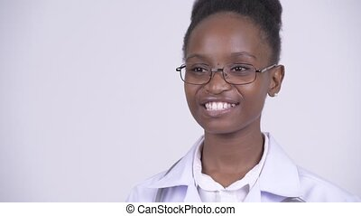Face of young happy African woman doctor thinking