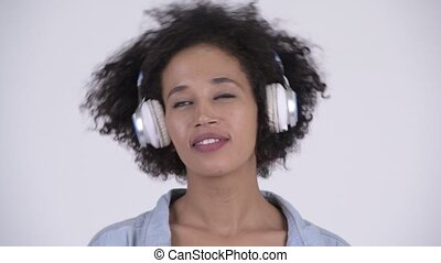 Face of young happy African woman listening to music