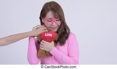 Face of young happy Asian nerd woman holding teddy bear and...