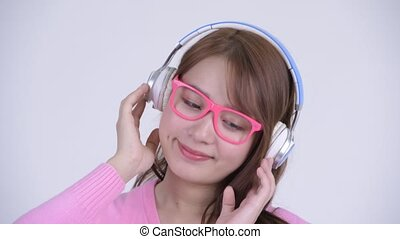 Face of young happy Asian nerd woman listening to music -...