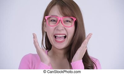 Face of young happy Asian nerd woman looking surprised