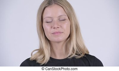 Face of young happy blonde woman relaxing with eyes closed -...