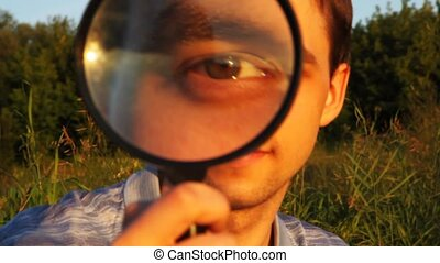 face of young man close through magnifying glass in park in summer
