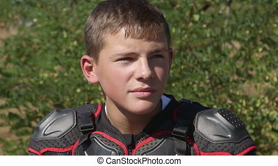 Face of young racer in motorcycle protective gear closeup