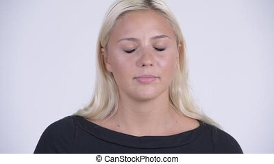 Face of young serious blonde woman nodding head no - Studio...