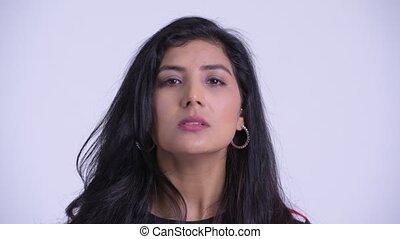 Face of young serious Persian woman nodding head no - Studio...