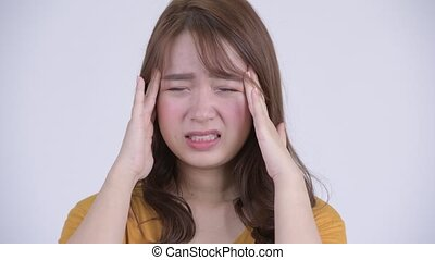 Face of young stressed Asian woman having headache