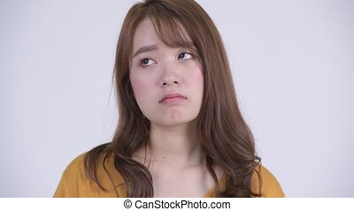 Face of young stressed Asian woman looking tired and bored