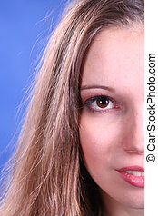 face of young woman on blue background