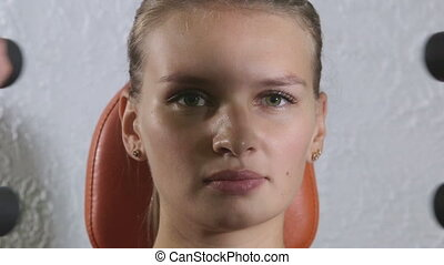 Face of young woman training on weight exercise machine in...