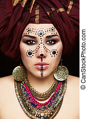 Portrait of young beautiful woman with traditional Berber face paint and turban