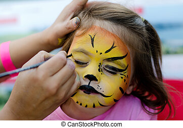 Cute little girl with face painted like a lion. Photo by Rafael Ben-Ari/Chameleons Eye